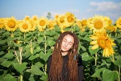 La ragazza di hippy gode del sole fra i girasoli fuori della città fotografia stock