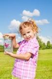 La ragazza di Lilttle tiene il barattolo con buterfly Fotografia Stock Libera da Diritti