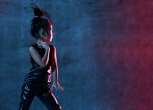 La ragazza di modello asiatica di alta moda alle luci uv-blu e porpora al neon luminose variopinte variopinte compone immagini stock