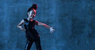 La ragazza di modello asiatica di alta moda alle luci uv-blu e porpora al neon luminose variopinte variopinte compone fotografia stock