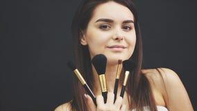 La ragazza di modello di bellezza, insieme della tenuta del truccatore di compone le spazzole e sorridere Bella giovane donna cas archivi video