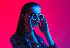 La ragazza di modo con capelli lunghi e gli occhiali da sole rotondi in un vestito brillante nero posa alla luce al neon nello st fotografie stock