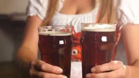 La ragazza di Oktoberfest mette due vetri della birra su una tavola di legno archivi video