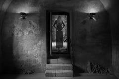 La ragazza di orrore in vestito nero compare in un torrione Fotografie Stock