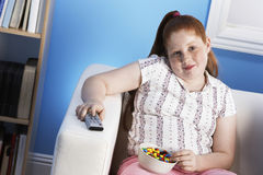 La ragazza di peso eccessivo con telecomando mangia gli alimenti industriali sullo strato Fotografie Stock