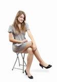 La ragazza di posizione in vestito grigio sopra bianco Fotografia Stock