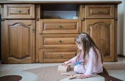 La ragazza di quattro anni in pigiama si siede su tappeto, costruzione facendo uso dell'giocattoli di legno, autosviluppo Fotografia Stock Libera da Diritti