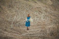 La ragazza di Redhair in vestito blu con il respiro del bambino fiorisce in primavera la foresta Fotografia Stock Libera da Diritti