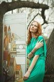La ragazza di Redhair in vestito verde posa vicino a vetro macchiato nella foresta di primavera Immagine Stock