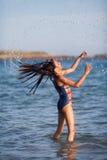 La ragazza di risata getta i suoi capelli bagnati attraverso l'aria Fotografie Stock Libere da Diritti