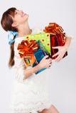 La ragazza di risata tiene le caselle con i regali. fotografia stock