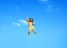 La ragazza di salto felice su una priorità bassa dell'azzurro Fotografia Stock