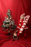 La ragazza di Santa Claus, il bastoncino di zucchero surdimensionato e l'albero di Natale Fotografia Stock Libera da Diritti