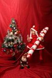 La ragazza di Santa Claus, il bastoncino di zucchero surdimensionato e l'albero di Natale Immagini Stock
