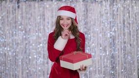 La ragazza di Santa con un regalo in sue mani mostra più tranquillamente il suo dito Priorità bassa di Bokeh Movimento lento stock footage