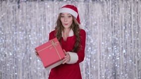 La ragazza di Santa tiene un regalo in sue mani e mostra un'approvazione del dito Priorità bassa di Bokeh Movimento lento stock footage