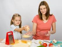 La ragazza di sei anni aiuta la madre a sfregare il formaggio grattugiato Fotografia Stock