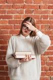 La ragazza di sforzo con i libri ha dimenticato qualche cosa di importante Immagini Stock Libere da Diritti