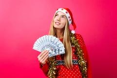 La ragazza di sogno in un maglione rosso ed in un cappello di Santa Claus, fa la p immagini stock