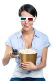 La ragazza di sorveglianza del film 3D passa il regolatore a distanza Immagine Stock