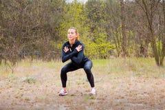 La ragazza di sport è impegnata nella forma fisica, riscaldamento Immagini Stock Libere da Diritti