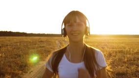 La ragazza di sport in cuffie è impegnata nel pareggiare, una ragazza sta preparandosi al tramonto e sta ascoltando musica stock footage