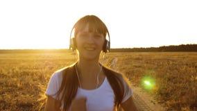 La ragazza di sport in cuffie è impegnata nel pareggiare, una ragazza sta preparandosi al tramonto e sta ascoltando musica archivi video
