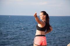 La ragazza di sport di forma fisica prepara i muscoli sulla spiaggia fotografia stock