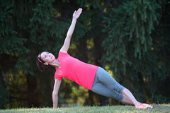 La ragazza di sport fa l'allenamento di esercizi all'aperto in parco Immagine Stock