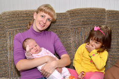La ragazza di tre anni con la gelosia esamina la sorellina sulle mani la madre fotografia stock libera da diritti