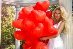 La ragazza di Valentine Beautiful con i palloni rossi ride, nel parco Bella giovane donna felice fotografia stock