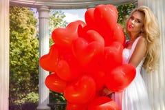 La ragazza di Valentine Beautiful con i palloni rossi ride, nel parco Bella giovane donna felice fotografia stock libera da diritti