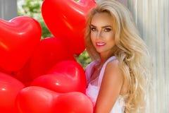 La ragazza di Valentine Beautiful con i palloni rossi ride, nel parco Bella giovane donna felice immagini stock