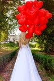 La ragazza di Valentine Beautiful con i palloni rossi ride, nel parco Bella giovane donna felice Festa di compleanno e sposa al fotografia stock