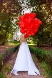 La ragazza di Valentine Beautiful con i palloni rossi ride, nel parco Bella giovane donna felice Festa di compleanno e sposa al immagini stock