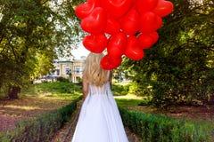 La ragazza di Valentine Beautiful con i palloni rossi ride, nel parco Bella giovane donna felice Festa di compleanno e sposa al immagine stock