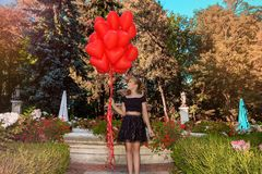 La ragazza di Valentine Beautiful con i palloni rossi ride, nel parco Bello bambino felice Festa di Natale Piccolo modello allegr immagini stock libere da diritti