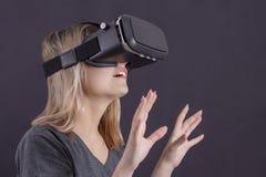 La ragazza di vetro di realtà virtuale in vetri di realtà virtuale è sorpresa immagine stock libera da diritti