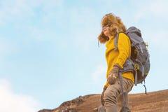 La ragazza di viaggiatore con zaino e sacco a pelo in occhiali da sole ed in un grande cappello di pelliccia nordico con uno zain Immagini Stock Libere da Diritti