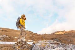 La ragazza di viaggiatore con zaino e sacco a pelo in occhiali da sole ed in un grande cappello di pelliccia nordico con uno zain Fotografia Stock