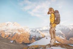 La ragazza di viaggiatore con zaino e sacco a pelo in occhiali da sole ed in un grande cappello di pelliccia nordico con uno zain Fotografie Stock