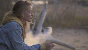 La ragazza di viaggio si siede sulla spiaggia ed ascolta musica video d archivio