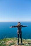 La ragazza di viaggio sta sull'orlo di alta scogliera sopra il mare Fotografia Stock Libera da Diritti
