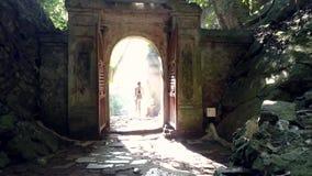 La ragazza di vista della parte lascia la vecchia caverna tramite il portone dell'arco stock footage