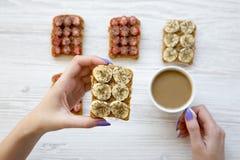 La ragazza di vista superiore sta tenendo il pane tostato ed il caffè del vegano sopra fondo di legno bianco fotografia stock