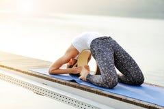La ragazza di yoga fa la posa di yoga del piccione sullo strumento della ruota Immagini Stock
