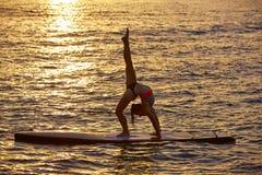 La ragazza di yoga sopra SUP sta sul bordo di spuma Fotografie Stock Libere da Diritti