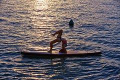 La ragazza di yoga sopra SUP sta sul bordo di spuma Immagini Stock