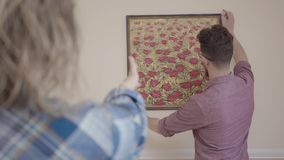 La ragazza dice un uomo barbuto con i vetri come appendere correttamente un'immagine sulla parete La giovane famiglia si muove ve stock footage