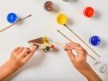 La ragazza dipinge la cabina gialla della pittura di un'automobile di legno Fotografia Stock